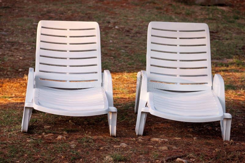 在地中海的异乎寻常的海滩,晒日光浴的白色塑料sunbeds和放松在草在度假旅馆热带庭院里  免版税库存照片