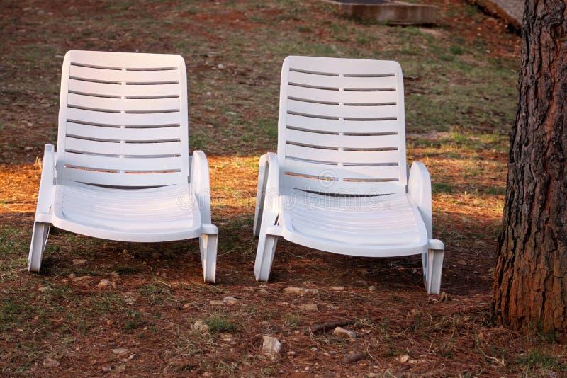 在地中海的异乎寻常的海滩,晒日光浴的白色塑料sunbeds和放松在草在度假旅馆热带庭院里  免版税库存图片