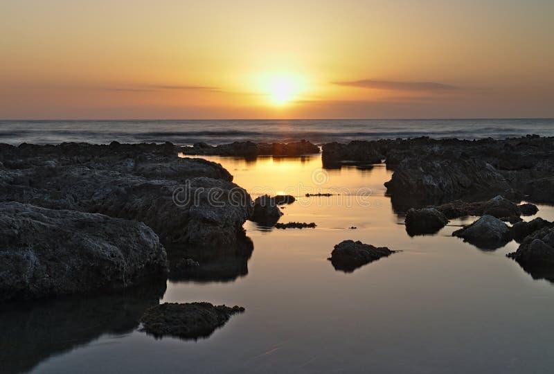 在地中海的日出,当剧烈的天空和岩石水池反射在前景的阳光,cala bona,马略卡,西班牙 库存照片