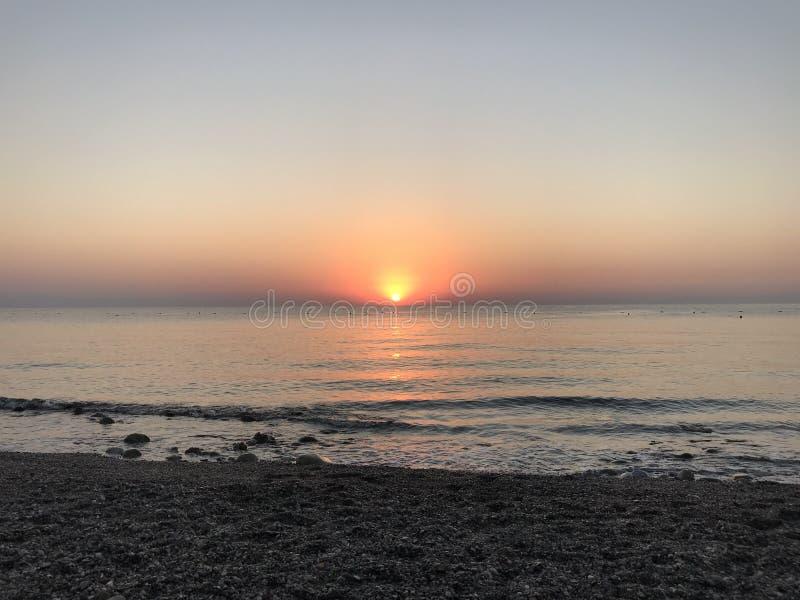在地中海的美好的桃红色日出Pebble海滩的 库存图片