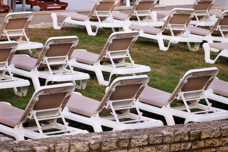 在地中海,晒日光浴的sunbeds的异乎寻常的海滩和放松在草在豪华旅游胜地旅馆热带庭院里  免版税图库摄影