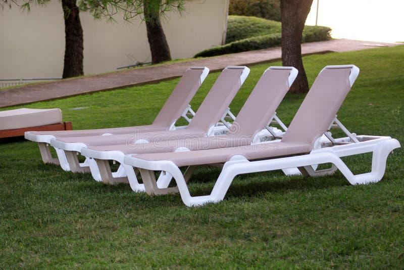在地中海,晒日光浴的sunbeds的异乎寻常的海滩和放松在草在豪华旅游胜地旅馆热带庭院里  库存照片