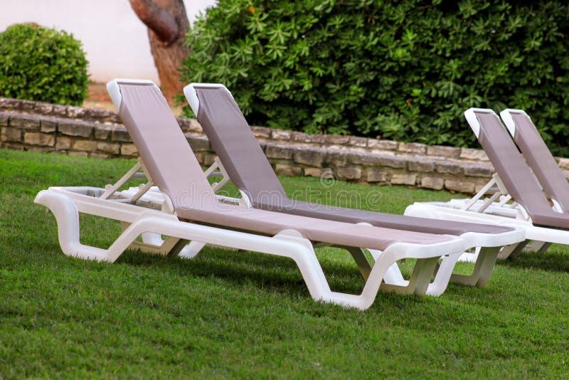 在地中海,晒日光浴的sunbeds的异乎寻常的海滩和放松在草在豪华旅游胜地旅馆热带庭院里  库存图片