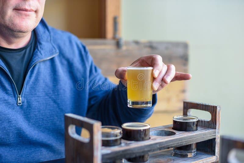 在地方microbrewery供以人员从飞行的采样啤酒 库存照片