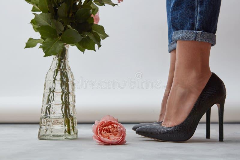 在地板上是一朵桃红色玫瑰,有绿色分支的一个玻璃花瓶在女孩的腿附近穿上鞋子与在上流的黑鞋子 库存图片