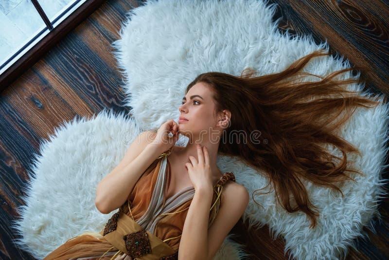 在地板上的一间屋子里的一个美丽的女孩的画象 免版税库存图片
