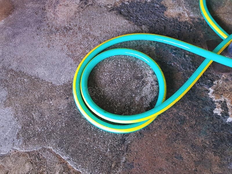 在地板上的五颜六色的绿色浇灌的水管 免版税库存照片