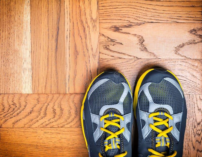 在地板上的体育鞋子 免版税库存图片