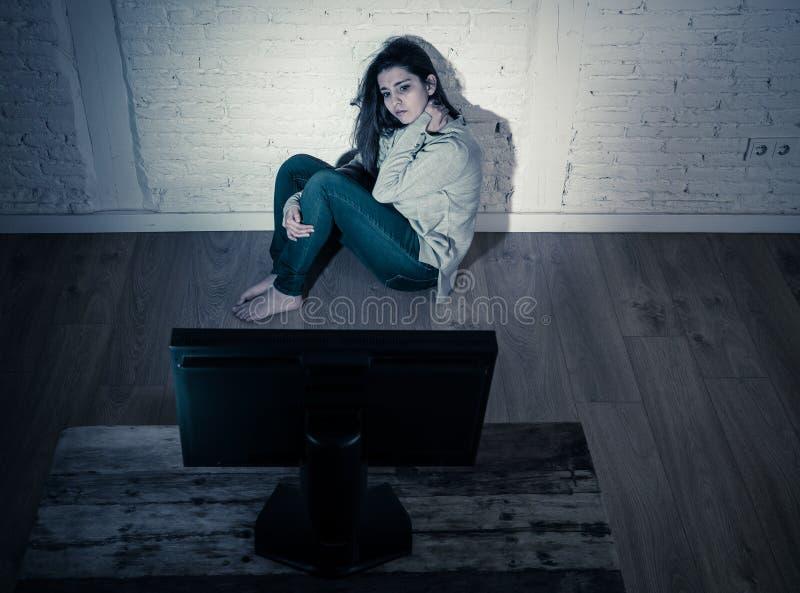 在地板上的凝视害怕的和哀伤的年轻女人计算机遭受的cyberbullying和骚扰 免版税库存照片