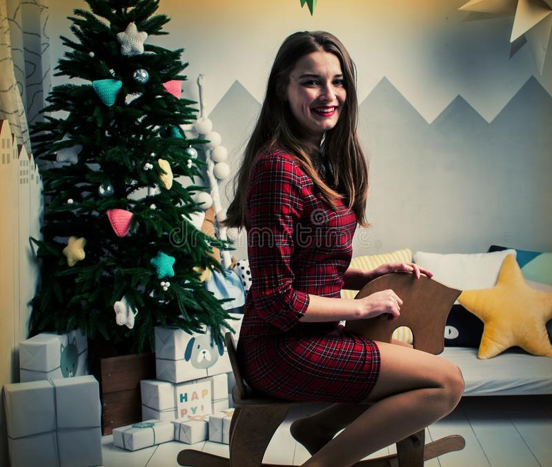 在地板上的十几岁的女孩在圣诞树下,男孩在心脏形状站立的灼烧的tealights中坐 库存照片