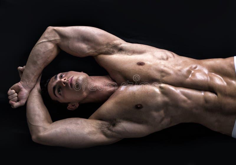 在地板上的可爱的年轻人与肌肉被剥去的身体 库存照片