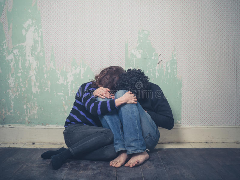 在地板上的哀伤的年轻夫妇 免版税图库摄影