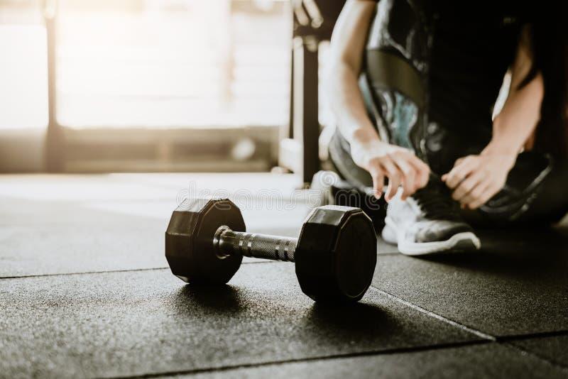在地板上的哑铃在与妇女的健身房在背景中的栓她的鞋带 免版税库存照片