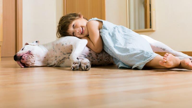 在地板上的小愉快的女孩与狗 免版税库存图片