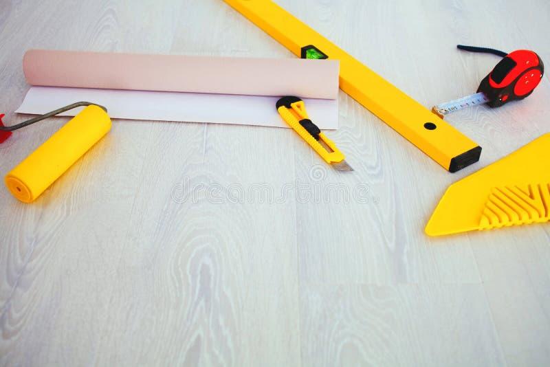 在地板上的工具为墙纸 免版税库存图片