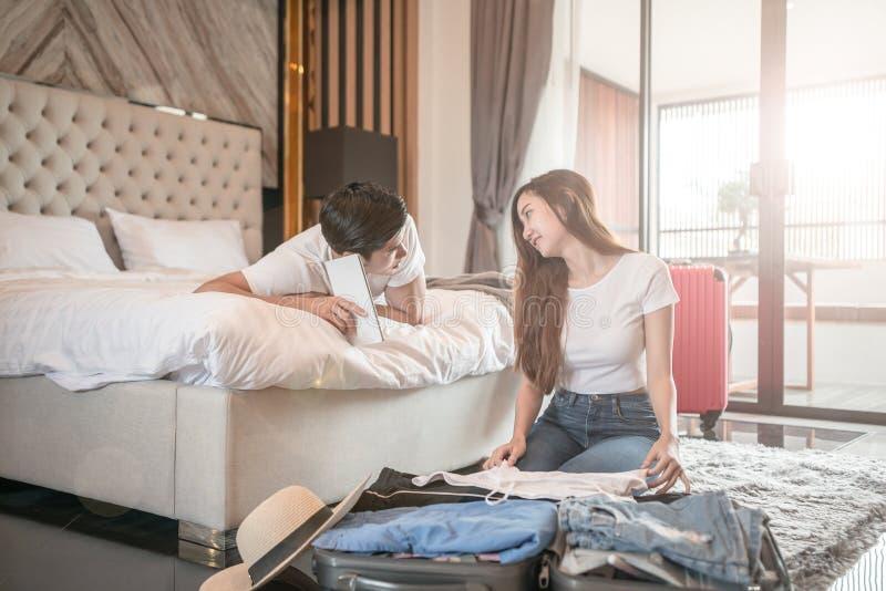 在地板上的愉快的夫妇包装手提箱在屋子查寻旅行旅行的用途片剂里在网上 图库摄影