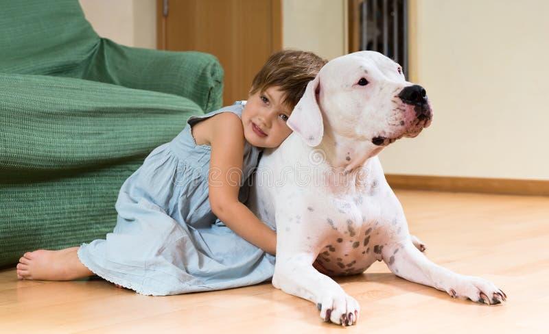 在地板上的愉快的女性小孩与狗 免版税图库摄影