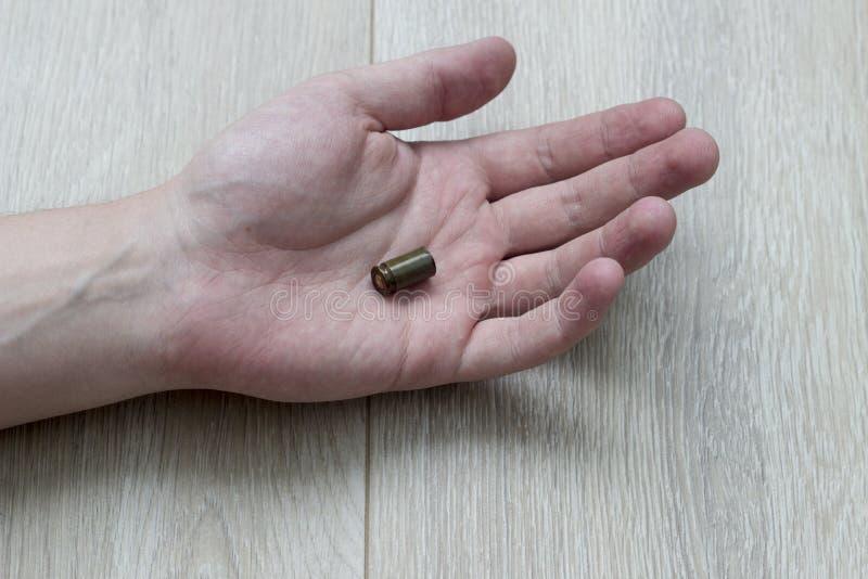 在地板上的手在说谎弹壳的棕榈,谋杀 免版税图库摄影