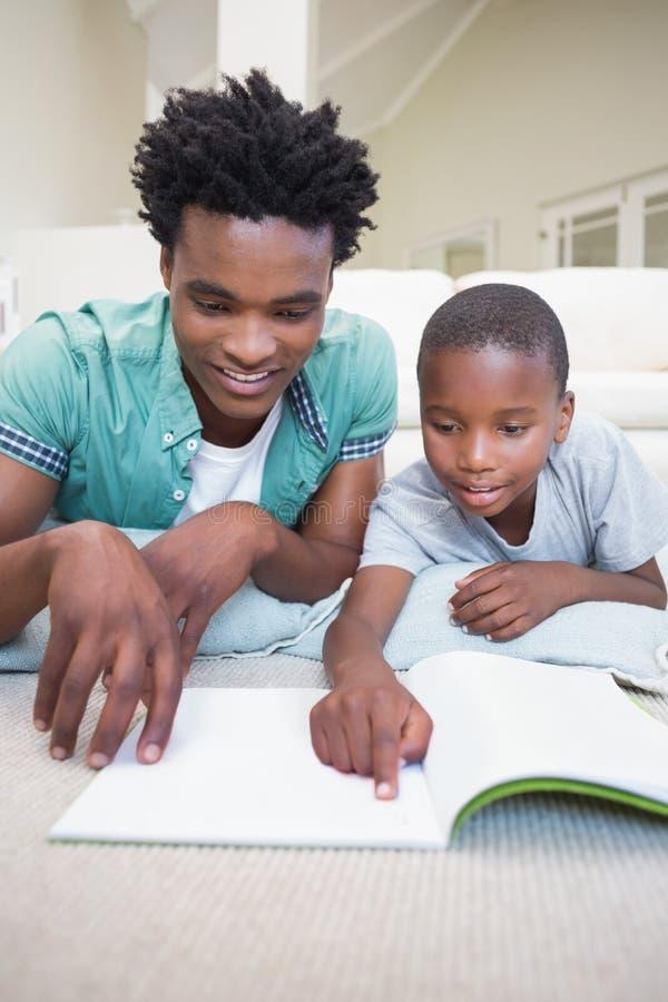 在地板上的父亲和儿子读书 库存图片