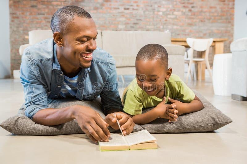 在地板上的父亲和儿子读书 免版税库存照片