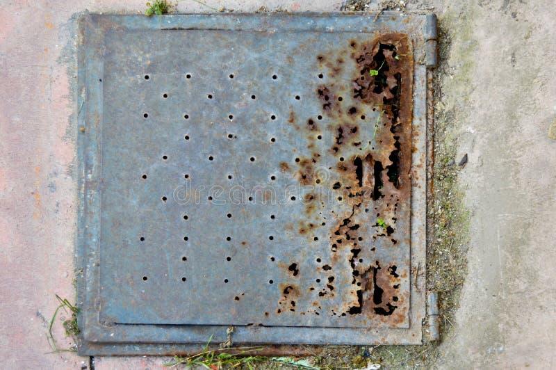 在地板上的生锈的金属人孔盖 免版税库存照片