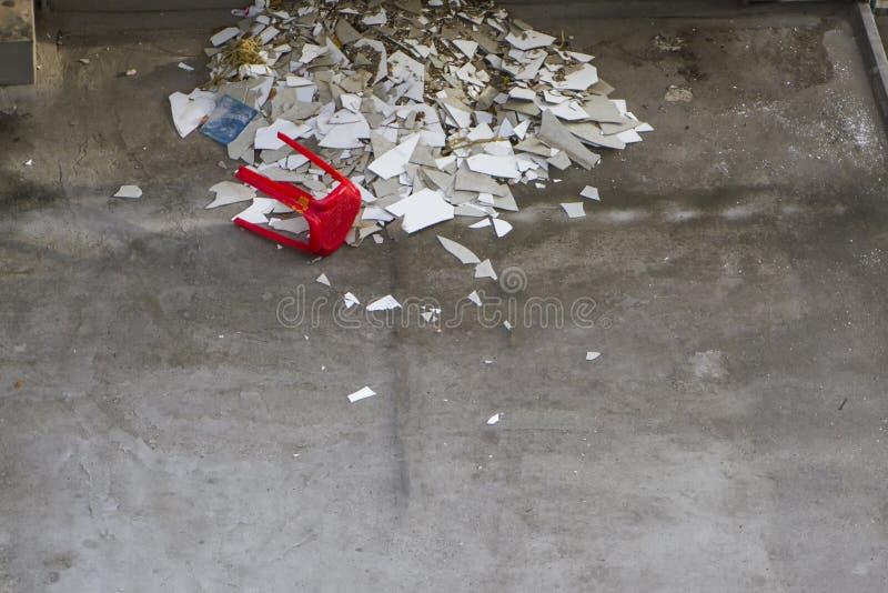 在地板上的白色打破的瓦片与红色椅子 库存图片