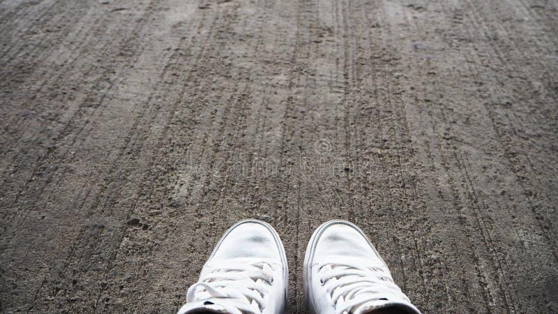 在地板上的白色鞋子 库存照片