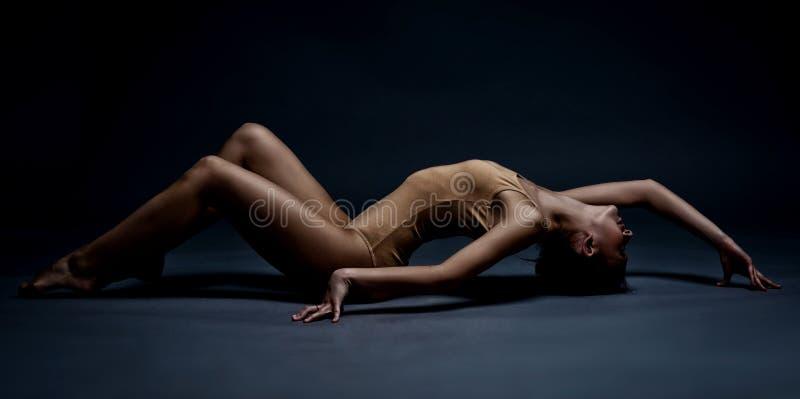在地板上的美丽的运动女孩 在行动的演播室画象 免版税图库摄影