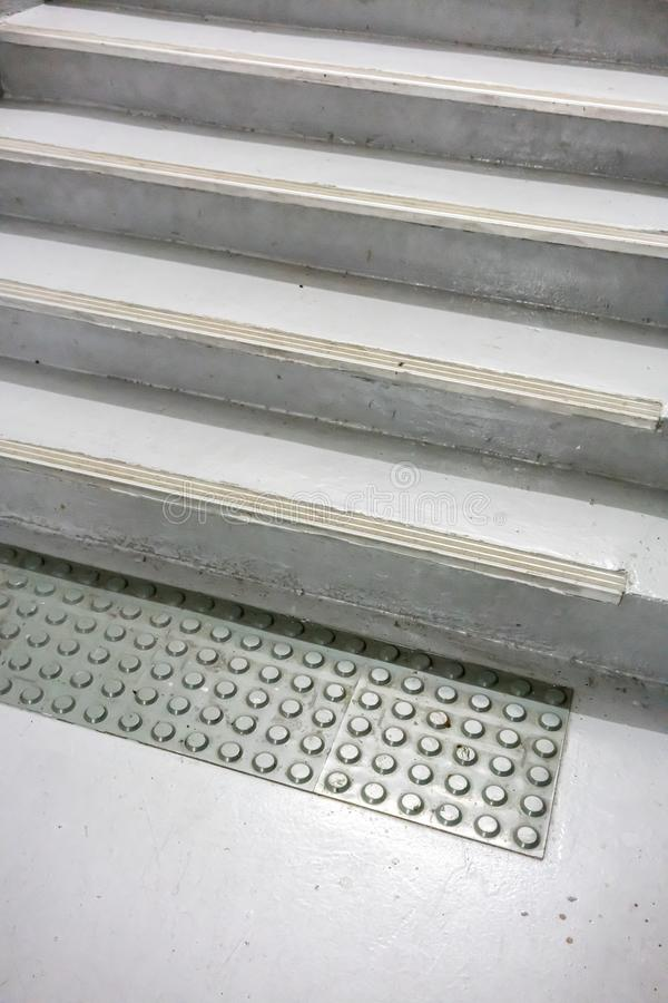 在地板上的老灰色不滑的席子对白色绘了楼梯被关闭 免版税库存照片