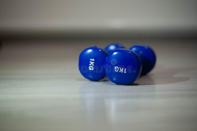 在地板上的蓝色哑铃 免版税库存照片