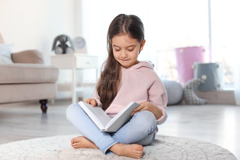在地板上的逗人喜爱的儿童看书 免版税图库摄影