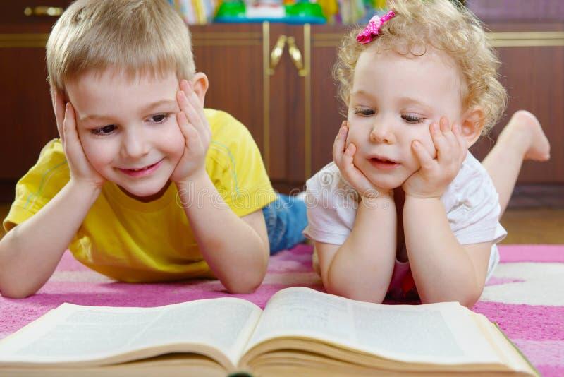 在地板上的逗人喜爱的小兄弟和姐妹阅读书 免版税图库摄影