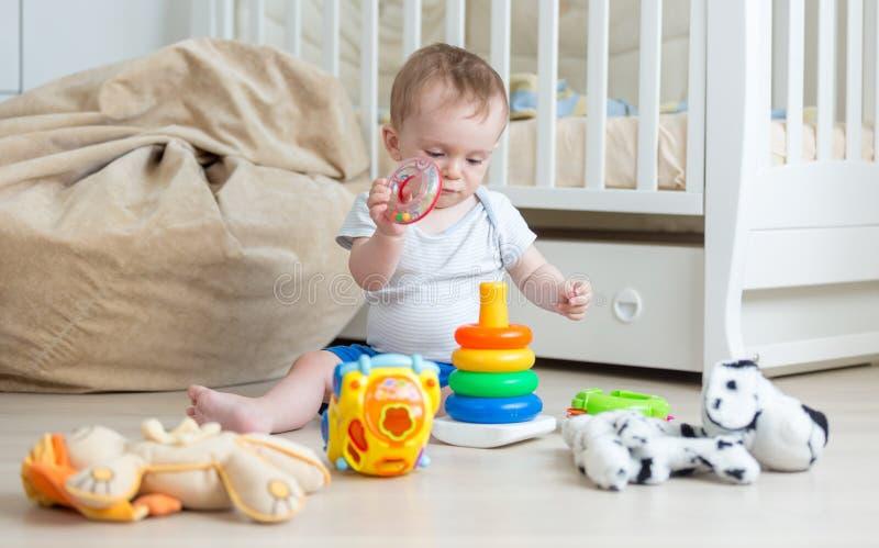 在地板上的逗人喜爱的男婴聚集的玩具塔 婴孩edu的概念 库存照片
