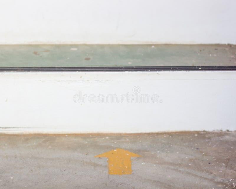在地板上的黄色箭头贴纸与拷贝空间 免版税图库摄影