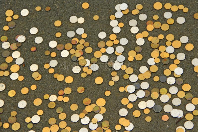 在地板上驱散的乌克兰硬币 黄色的金属货币白色和 小硬币 免版税图库摄影