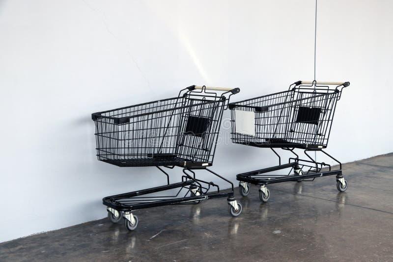 在地板和白色背景上的黑购物车 台车是商店供应的推车,特别是超级市场 库存照片
