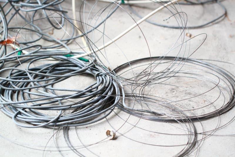 在地板整修装饰的废弃的被放弃的被破坏的被放弃的LAN缆绳导线卷圈子绳索再磨光垃圾垃圾 免版税库存照片