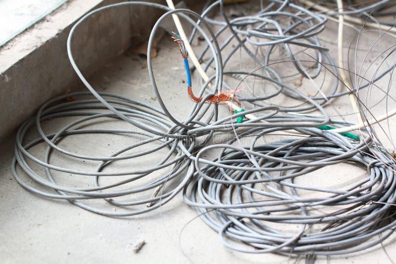 在地板整修装饰的废弃的被放弃的被破坏的被放弃的LAN缆绳导线卷圈子绳索再磨光垃圾垃圾 库存图片