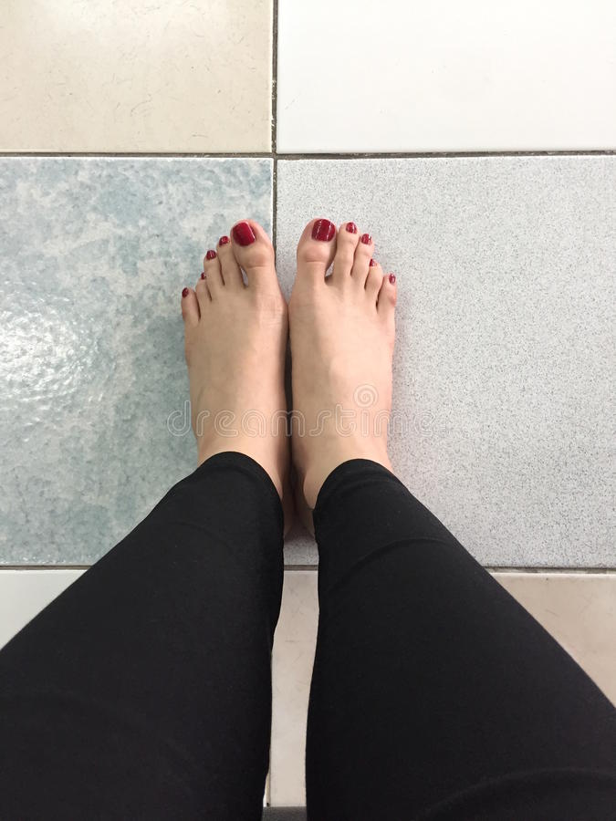 在地板背景的Selfie赤脚室外红色钉子 免版税库存图片