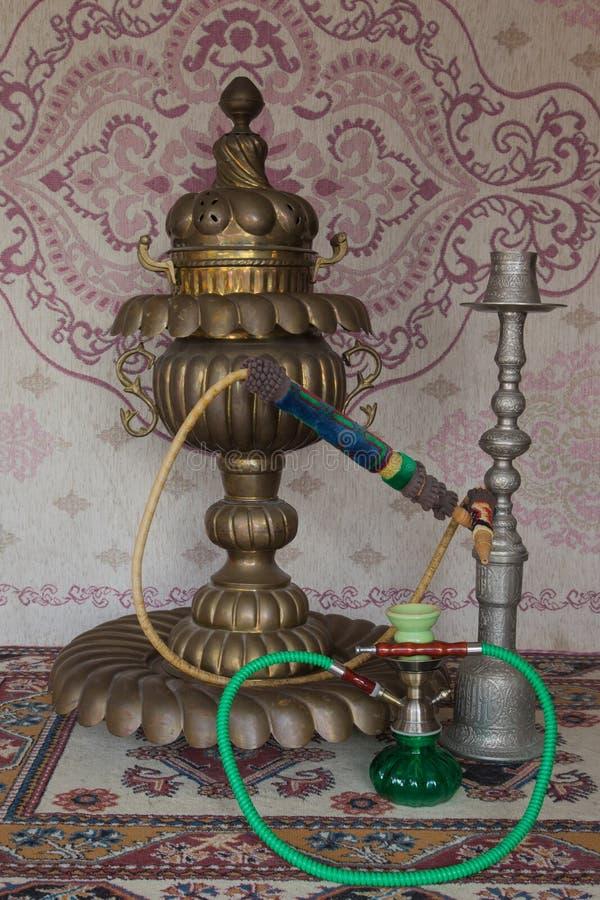 在地毯前面的三葡萄酒水烟筒 库存照片