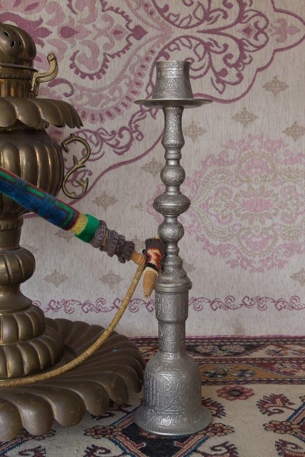 在地毯前面的铝葡萄酒水烟筒 图库摄影