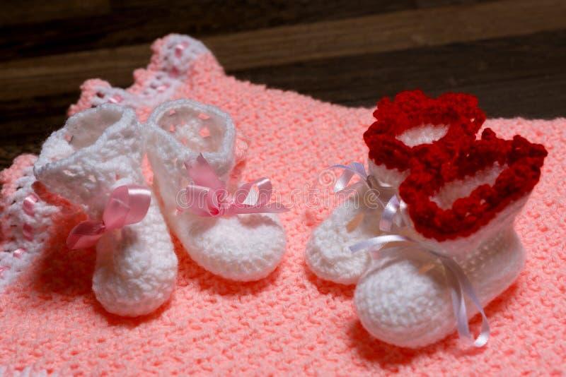 在地毯桃红色的婴孩小的鞋子 免版税库存照片