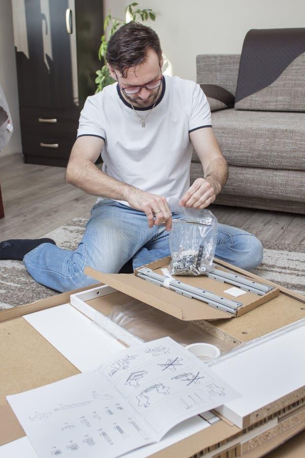 在地毯的人跪在有家具的元素的纸板箱上自动装配和裁减剪刀的有塑料的 库存图片