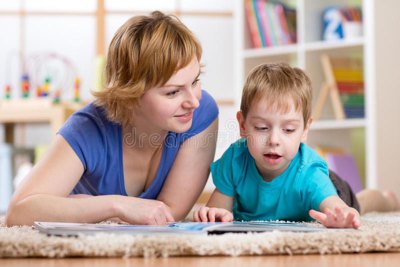 在地毯的妈妈和儿子读书在屋子里 免版税库存图片
