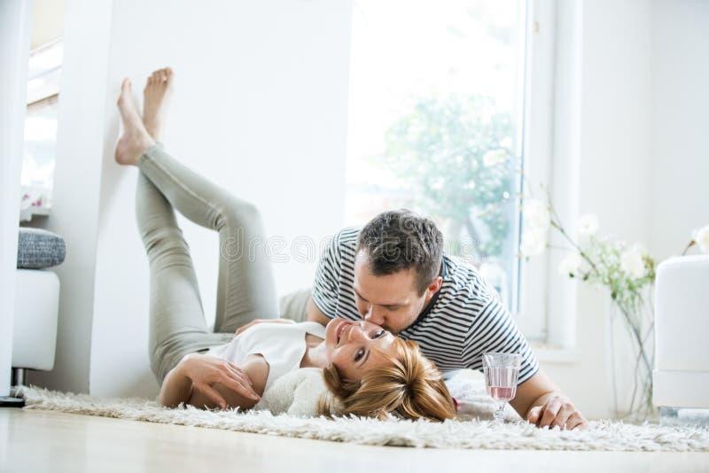 在地毯的客厅的年轻夫妇 免版税图库摄影