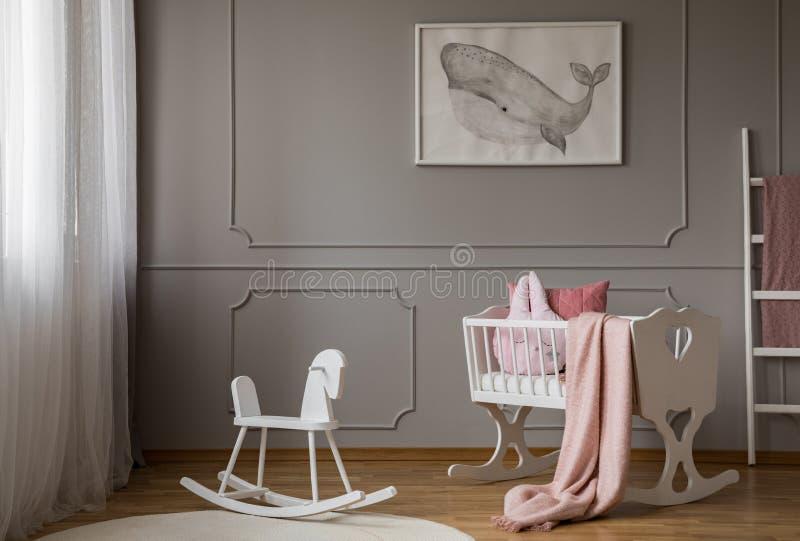 在地毯的摇马在灰色孩子的卧室内部的摇篮旁边与鲸鱼海报 实际照片 图库摄影