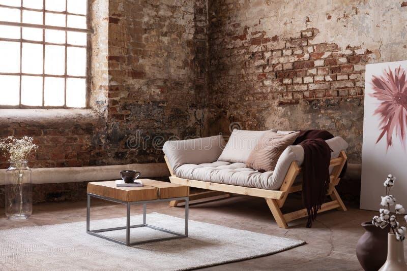 在地毯的木桌在wabi sabi客厅内部的灰色长椅旁边与海报和窗口 图库摄影