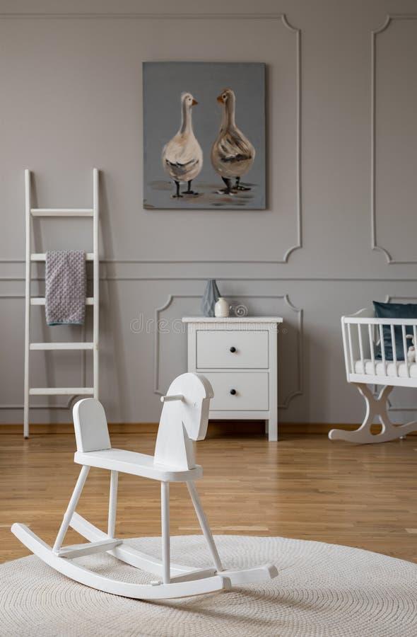 在地毯的白色摇马在婴孩的卧室内部 库存图片