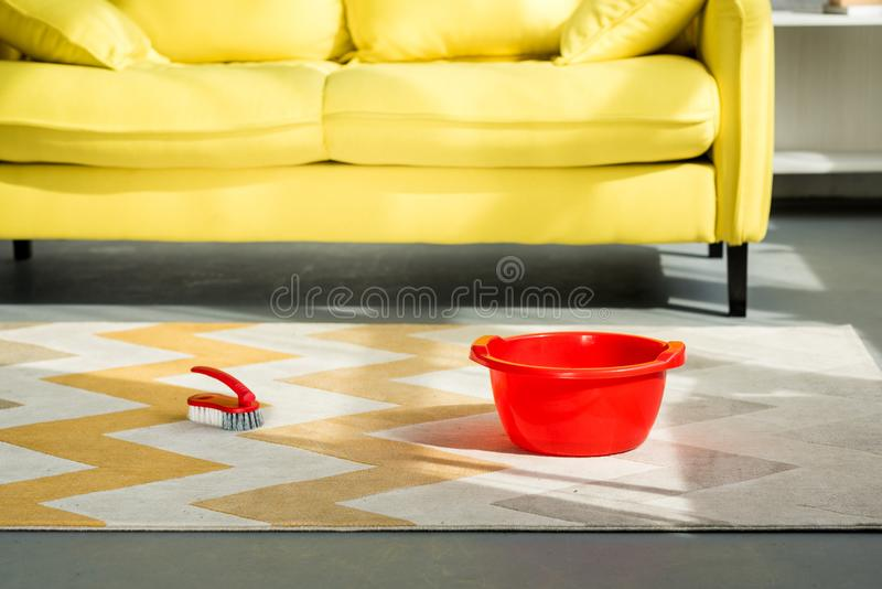 在地毯的红色桶和清洁刷 库存照片