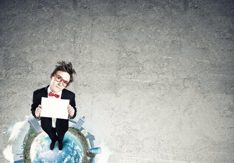 在地球上面的可笑的商人 免版税库存照片
